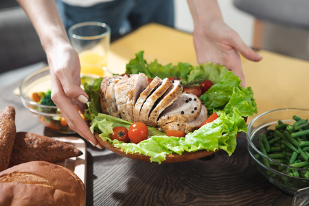 Close up of female hands holding plate with fresh meat and vegetables under the desk in kitchen  Stock Photo