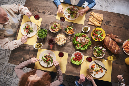 Top view of festive wholesome dishes lying on table. Household members are eating vegetables, salads, meat, bread, rice and drinking red wine Stock Photo