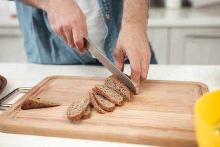 Close up of male hands cutting fresh bread with crust into thin pieces on wooden board. Man is holding knife while standing at table