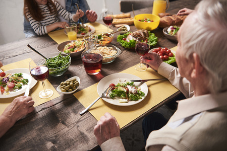 Close up of festive dinner consisting of healthy dishes. Elderly male is eating salad and holding glass with red wine. He is sitting opposite to his grandchild Stock Photo