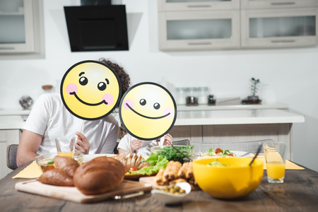 We like healthy food. Portrait of happy father and daughter having lunch together at home. They are sitting at table and holding positive smiles near their faces  Stock Photo