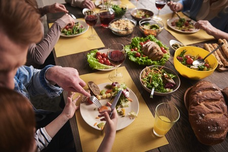 Close up of dinner table full of healthy dishes. Father sitting next to daughter and showing her how to use knife and fork. They are having salad with vegetables