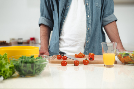 Close up of red tomato on wooden board. Man is standing at table in kitchen while cooking healthy lunch