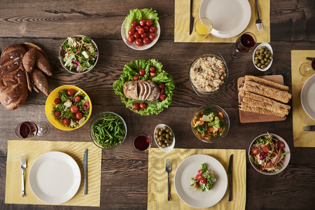 Top view of served table for four persons with wholesome meal. Tasty salads, bread, lots of vegetables, meat and rice lying with red wine and juice Stock Photo