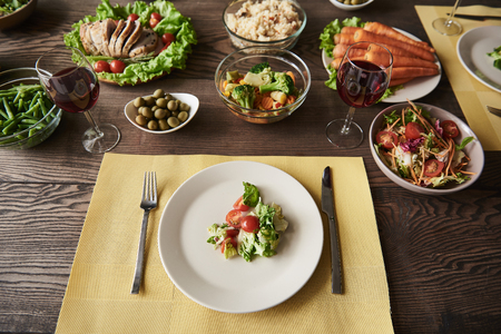 Top view of big brown table with white plates and bowls of healthy food. There are carrot, asparagus, tomatoes, lettuce, broccoli, olives, whole grain bread, baked meat and rice