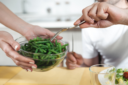 Close up of woman hands holding a bowl with stewed green beans inside. Man is taking vegetable by fork