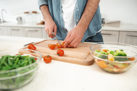 Close up of male arms cutting tomato for salad. He is standing at table and holding knife