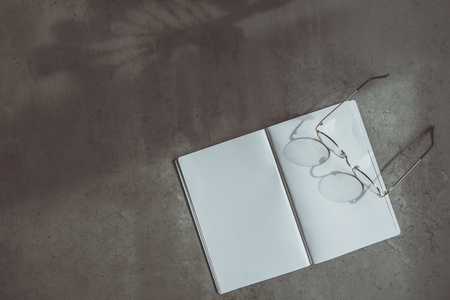 Top view contemporary spectacles on notebook situating on concrete surface