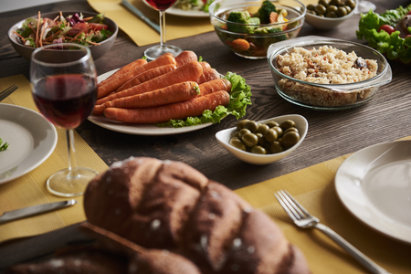 Close up wholesome meal served on table. Plate of carrot, rice with spices, green olives, and veggie salad lying on dining board in the middle with white plates and glasses of red wine nearby