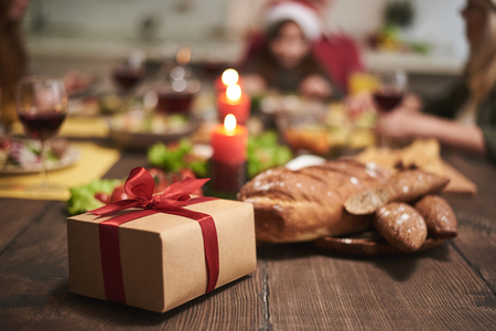 Focus of gift with red ribbon put on wooden board full of festive dishes. Box and candles creating festive atmosphere for dinner