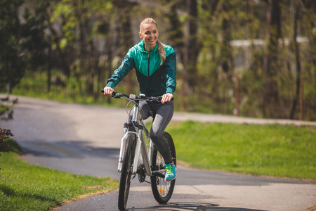 Young pretty lady is riding bike in park and smiling. She is enjoying sunny weather and environment around her. Copy space in right side