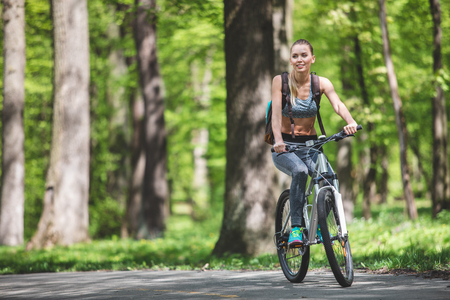 Full length portrait of vigorous lady is backpacking in marvelous nature on bicycle. She is slowly pedaling with her backpack and watching surrounding environment