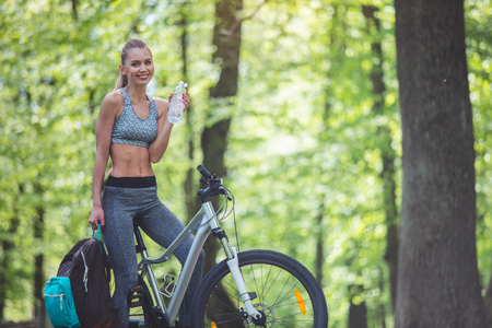 Thirsty lady is having bottle of water and smiling while drinking. She is riding bike in green nature and carrying backpack. Copy space in right side