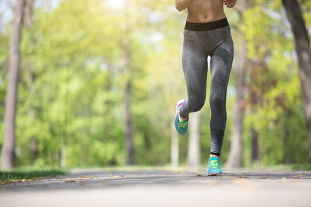 Close up of female legs who is running outside. She is actively spending time training along wide road in forest. Copy space in left side Banque d'images - 103903407