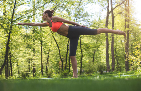 Athletic calm lady is practicing yoga position among greenery outdoors. She is balancing on one foot while listing back other one. She is stretching one arm ahead and looking forward with joy