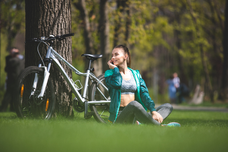 Relaxed lady is sitting on green grass in park and speaking on mobile phone. Her bicycle is leaning against big tree besides her. Sporty girl is crossing legs and enjoying moment Stock Photo