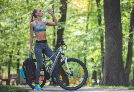 Athletic woman is quenching thirst while cycling in marvelous park. She is sitting on bicycle and holding rucksack. Copy space in right side 版權商用圖片