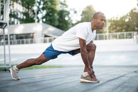 Full length portrait of concentrated young man doing exercise on open air Stock Photo