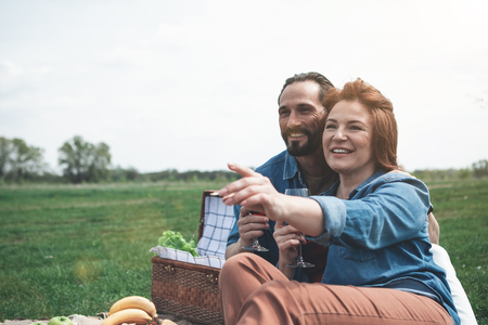 Look at it. Portrait of glad mature woman is pointing finger at beautiful landscape and smiling. Man is embracing her with love. They are sitting on the meadow with relaxation