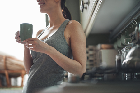 Low angle of female hands holding cup of hot drink. Smiling girl is standing and enjoying leisure at home Stock Photo