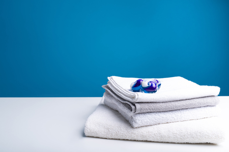 Best result. Close up of light soften towels folded in pile. Capsules with washing liquid inside lying on top. Copy space in left side Stok Fotoğraf
