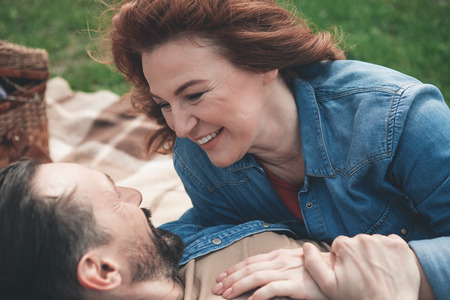 Joyful mature loving couple is having fun in the nature. They are lying on blanket on grass and cuddling. Lovers are looking at each other with love and smiling