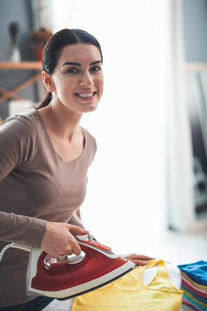 Waist up portrait of beautiful brunette lady with red iron. Joyful woman is pressing yellow t-shirt and looking at camera with smile