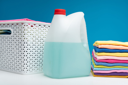 Close up of container of bleach lying on white table at colorful t-shirts folded in pile. Wicker basket is aside
