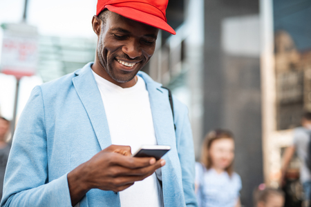 Outgoing young man typing in modern mobile while walking around city