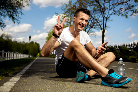 Smiling guy is using headphones and smartphone while sitting on asphalt among green trees. He is having bottle of water besides and demonstrating victory sign. Man is wearing smartwatch and winking