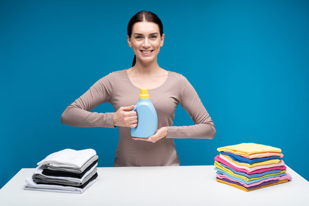 Sensible solution. Waist up portrait of merry housewife standing with bottle of washing liquid in hands. She is at big white table with clean clothes sorted in two piles Banque d'images - 103904341