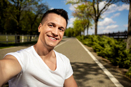 Portrait of cheerful handsome guy smiling to camera while making selfie. He is enjoying free time while walking along asphalt road in sunny park Stock Photo