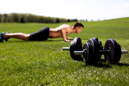 Selective focus on pair of dumbbells lying on green lawn while man is exercising with his own weight on background. Sportsman is doing push-ups among beautiful nature