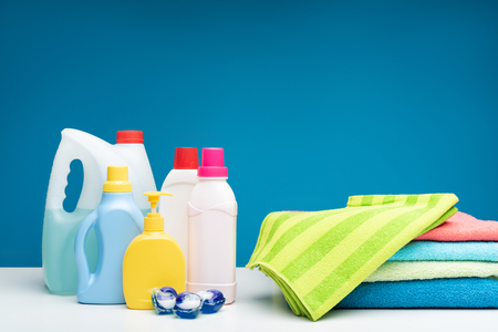 Bright bath towels pile covered with green one. Range of different detergents standing nearby