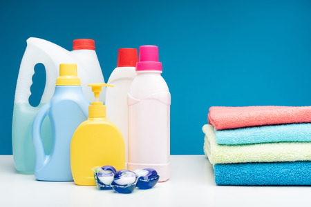Pick the one you like. Close up of selection of washing liquids put on white surface. Folded pile of towels is lying nearby