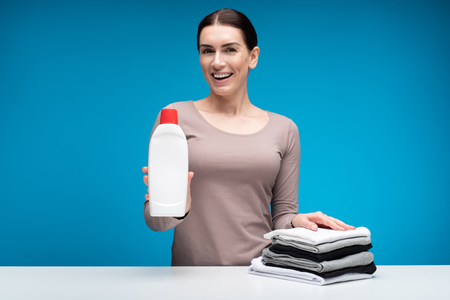 Waist up portrait of smiling housewife demonstrating washing liquid with smile. She is standing at table with folded black and white t-shirts with content. Copy space in left side Stock Photo