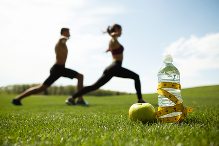 Man and woman are doing lunges together on background. Healthy lifestyle for male and female concept