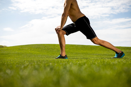 Athletic shirtless man is doing work out in fresh air. He is stretching with lunges and warming-up. Exercising in nature on warm day concept