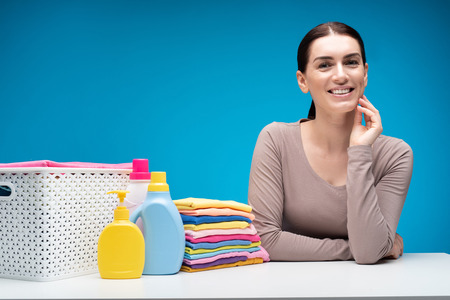 Waist up portrait of smiling brunette woman standing at laundry table isolated on blue background. She is touching right cheek with joy. Pile of colorful folded garments and washing liquids are nearby Stock Photo