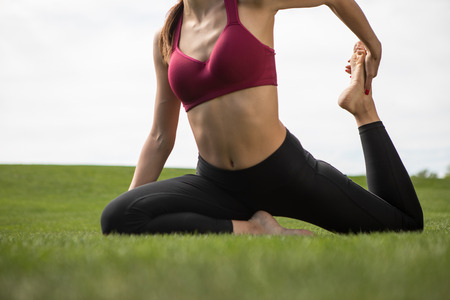 Slim woman is doing stretching while sitting on grass. She is bending leg and pulling it with hand for training flexibility on lovely warm day Reklamní fotografie