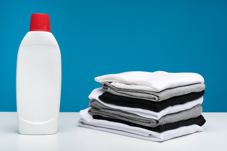 Close up of grey, black and white washed clothes folded in pile lying on board. Bottle of laundry gel is aside Stock Photo