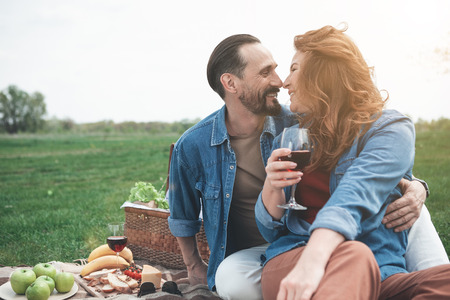 Happy loving couple is touching nose to nose with gentleness. Man is looking into woman eyes with love and smiling. They are sitting on grassland and hugging