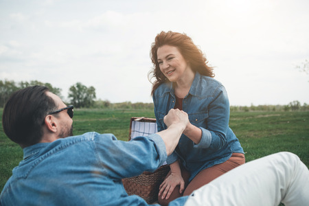 Cheerful loving couple is holding hands with gentleness while relaxing on the meadow. Lady is looking at husband with love and smiling