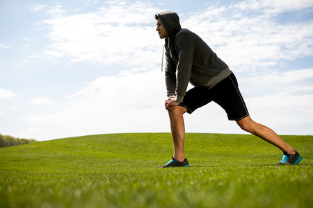 Concentrated man is doing lunges on green lawn during lovely day. He is stretching and warming-up on grass while looking ahead. Copy space in left side