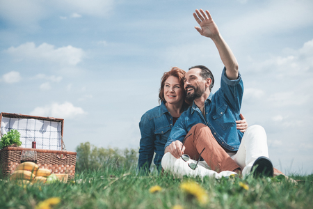 Hello. Cheerful mature man is waving hand to someone while sitting on blanket with his wife. Woman is embracing man and smiling. They are having picnic on the meadow 写真素材