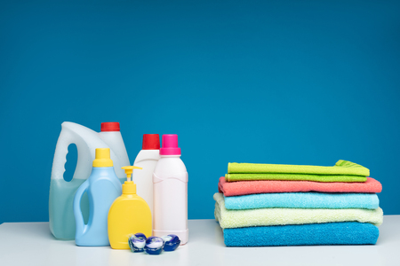 Best means for colourful laundry. Pile of terry bath linens lying beside washing capsules, liquids, bleach and soap