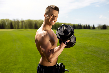 Smiling man is having fun during training with sport equipment. Strong male is lifting dumbbells for biceps relief and power. He is standing topless among green landscape while wearing smartwatch