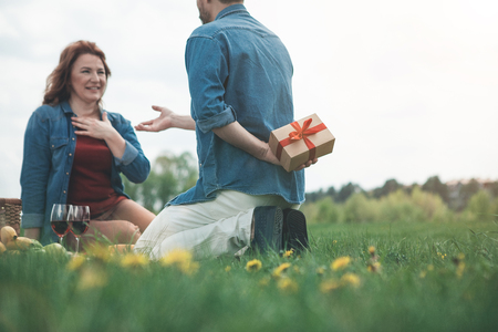 I prepared gift for you. Low angle of happy man hiding a box behind his back. Woman is looking at him with surprise and smiling. Lovers are sitting on grass in the nature
