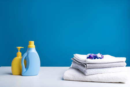 Conventional vs. modern. Washing liquid and soap standing on one side of surface. Pile of soft towels with capsules for cleaning on top of it on the other side of table