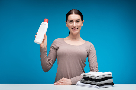 You can trust it. Waist up portrait of smiling female isolated on blue background. She is standing with bottle of washing liquid in hands showing its quality. Black and white clothes lying aside